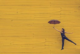 stock image of woman, umbrella, yellow background