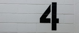 stock image of a number 4 painted on a brick wall